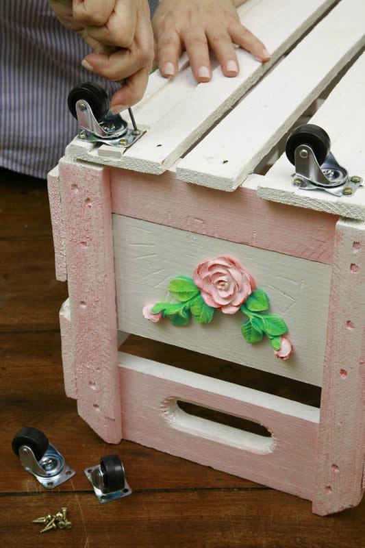 colocando rodinhas no caixote da madeira