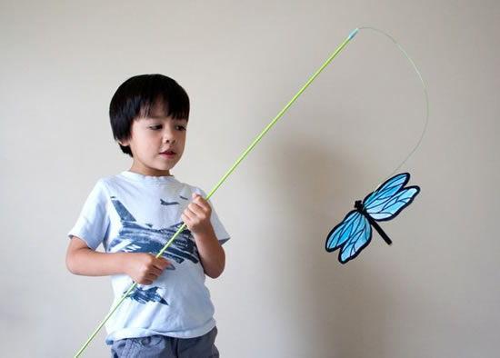 Criança brincando com borboleta de papel