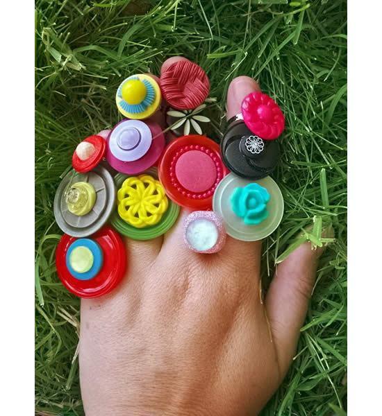 Mão com anéis de botões artesanais