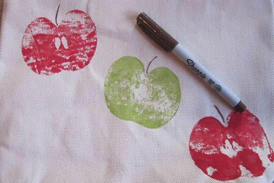 Fazendo talinhos nas maçãs decoradas na sacola com piloto marcador