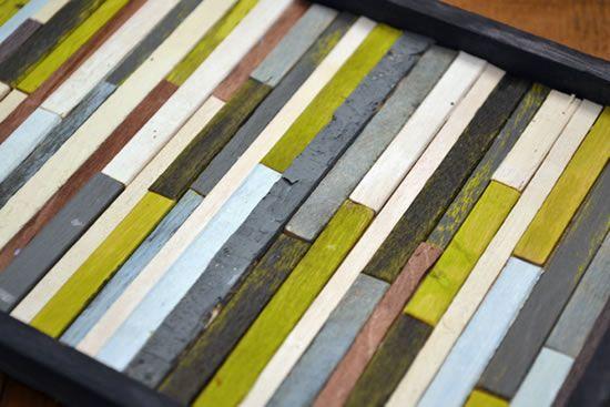 Colando os palitos de picolé coloridos para decorar a sala de estar