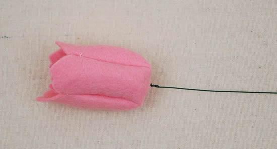 Colocando botão na flor de feltro