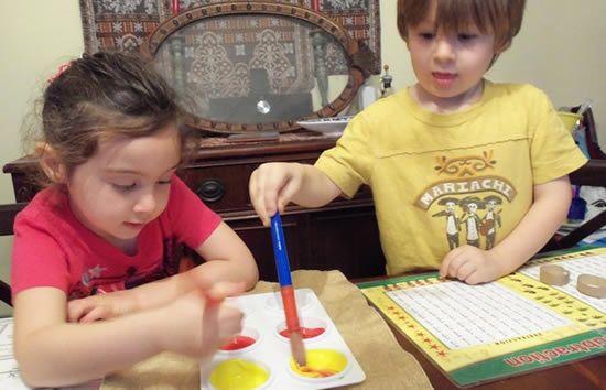 Crianças com tinta para pintar abobora de papel para Halloween