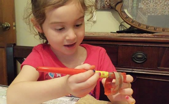 Criança pintando o rolinho de papel