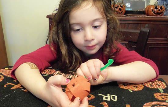 Menina fazendo artesanato para Halloween