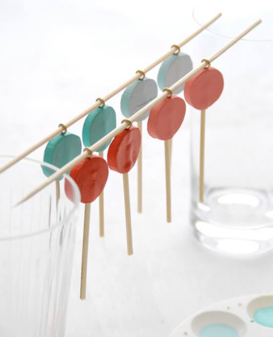 Pirulitos pintados e secando para colocar o glitter