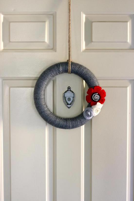Guirlanda de linha de crochê, feltro e coroa de isopor fazendo a decoração da porta de casa
