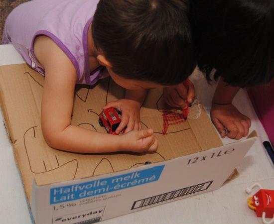Criança brincando na caixa de papelão