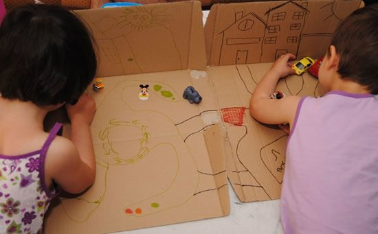 Criança brincando na caixa de papelão decorada
