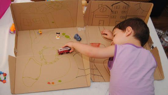 Brincando com carrinhos na caixa de papelão