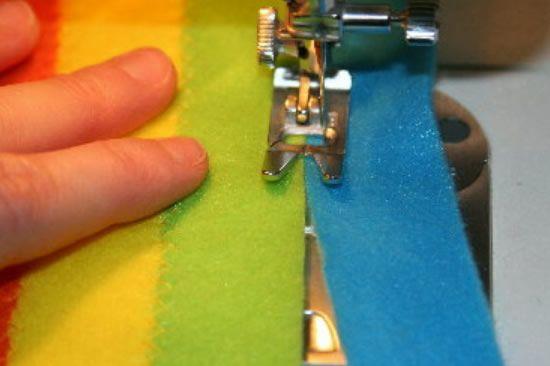 Costurando os feltros coloridos para fazer o arco-íris