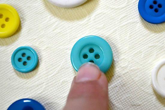 Pressionando o botão com o dedo para colar no quadro