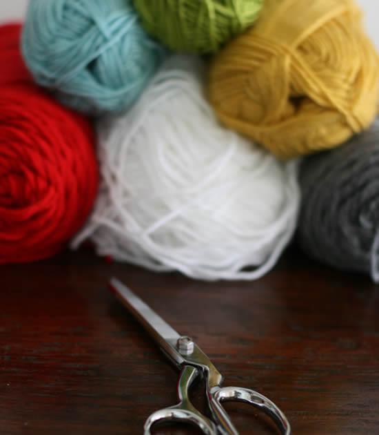 Novelos de lã coloridos e uma tesuora