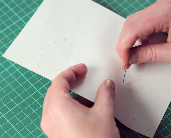 Furando papel de ofício para fazer cartão