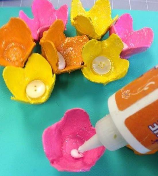 Colocando o botão em cada florzinha artesanal e reciclada