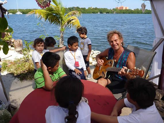 Rishi tocando violão na ilha de garrafas PET
