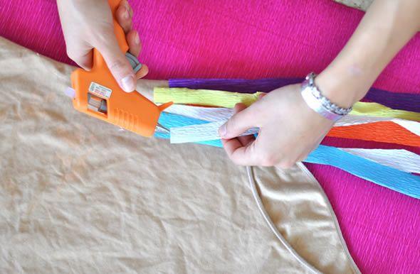 Colando as tiras de papel crepom para fazer a saia