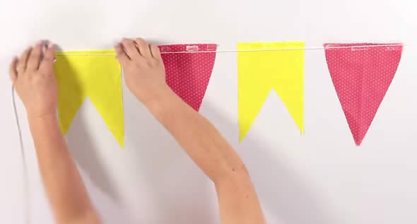 Colando as bandeirinhas de São João