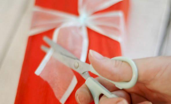 Cortando a fita de tecido para fazer presente