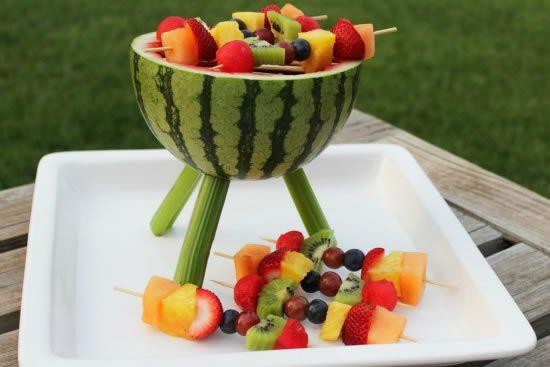 Acomode os espetos de madeira com as frutas sobre a composição que ...