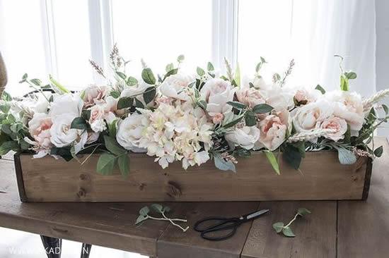 Decoração com arranjo de flores e caixotes de madeira